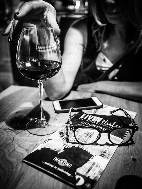 Glass of red wine on table with spectacles