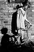 A girl with her bike, her and another child's shadow, UK, 1980s