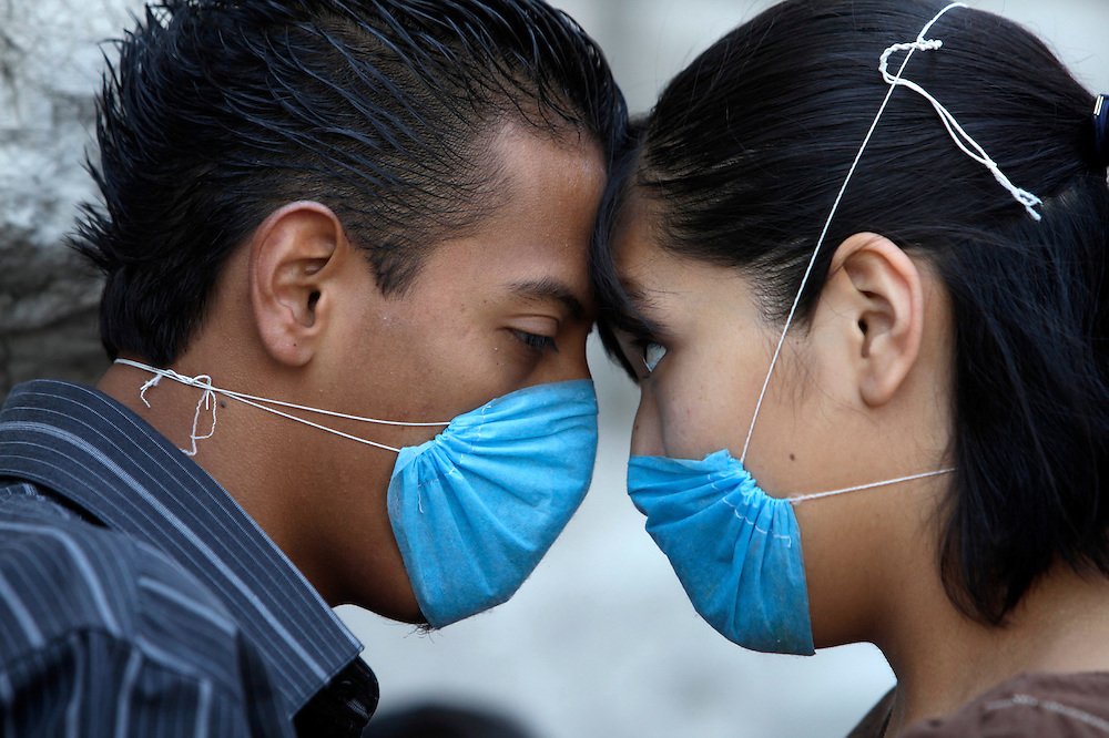 A couple wait to be attended by doctors in a mobile clinic set up to serve people with symptoms of swine flu, Mexico City, Thusday, April 30, 2009. (AP Photo/Rodrigo Abd)