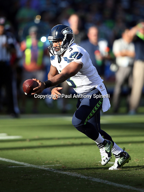 Seattle Seahawks quarterback Russell Wilson (3) hands off the ball on a running play as the late day sunlight leaves shadows across the field in the second quarter during the 2015 NFL preseason football game against the San Diego Chargers on Saturday, Aug. 29, 2015 in San Diego. The Seahawks won the game 16-15. (©Paul Anthony Spinelli)