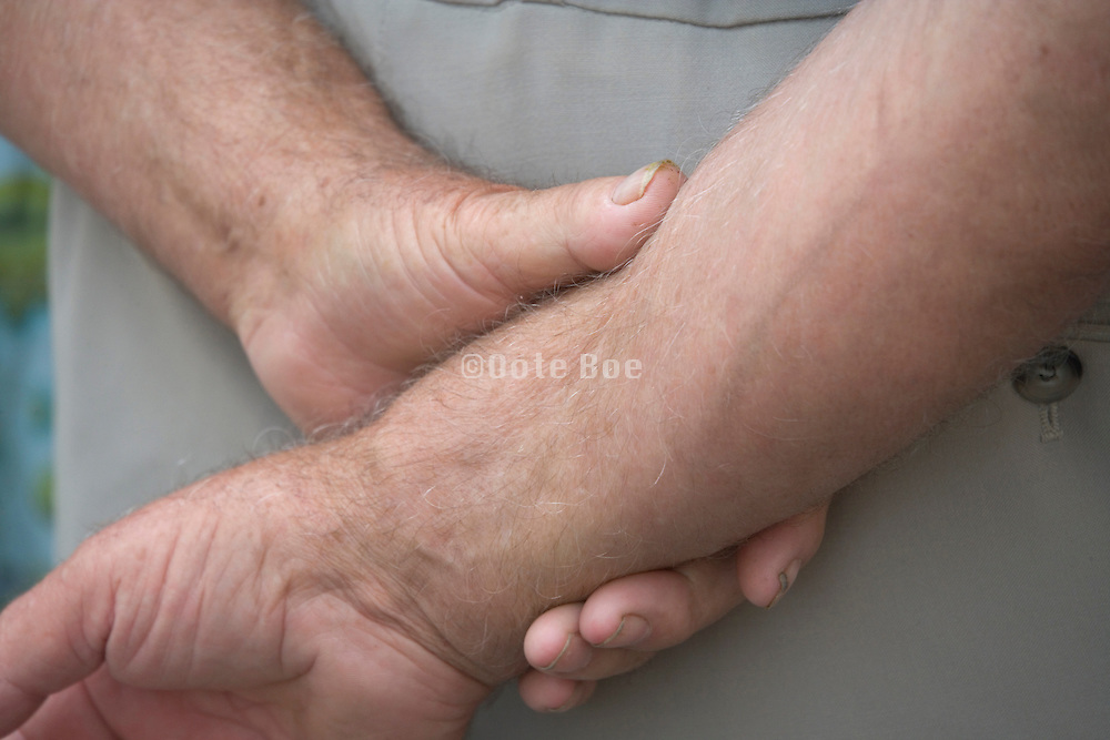 person standing with his hand clasped behind his back