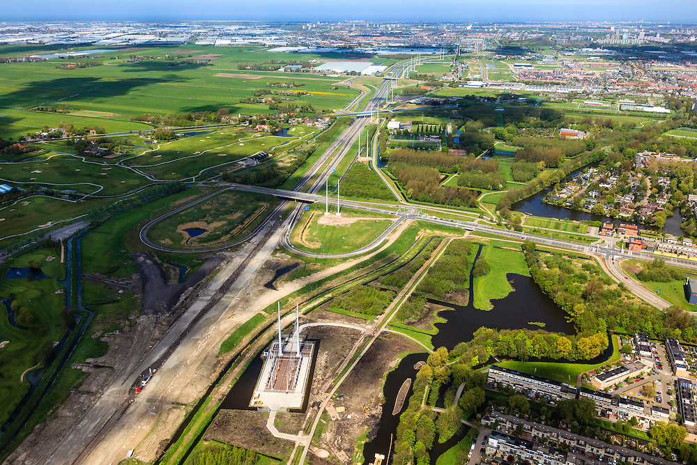 Nederland, Zuid-Holland, Delft, 09-05-2013; aanleg verlengde A4 Midden-Delfland. Den Haag aan de horizon..Naast de rijksweg onderstation en masten van het landelijke koppelnet Randstad 380 tracé van netbeheerder Tennet met het nieuwe type hoogspanningsmast (Wintrack, ontworpen door Zwart-Jansma) .Construction extension A4 motorway through the polder between Delft and Rotterdam. The Hague on the horizon..New type High Voltage Pylon (design Zwart-Jansma) for 380 kV circuit in the Randstad next to the new motorway..luchtfoto (toeslag op standard tarieven).aerial photo (additional fee required).copyright foto/photo Siebe Swart