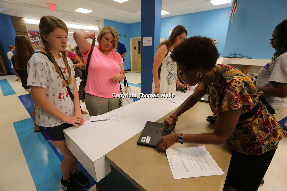 Retta Maxwell, 17, and her mother, Tina, pcik up her computer from Joan Kelsie as students get ready for the upcoming school year.