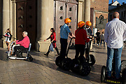 Tourist on Segways listen to their tour guide outside the Church of St Mary on Rynek Glowny market square, on 22nd September 2019, in Krakow, Malopolska, Poland.