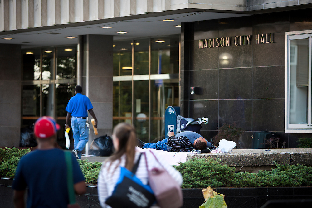 MADISON, WI — SEPTEMBER 14: A homeless man rests in front of the City County Building at the close of business in downtown Madison, Monday, September 14, 2015.