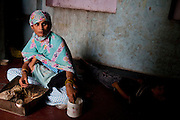 Nafeesa, 27, breastfeeds her youngest of 4 children while she rolls bidis (indian cigarettes) in her house in a slum in Tonk, Rajasthan, India, on 19th June 2012. Nafeesa's health deteriorated from bad birth spacing and over-working. While her husband works far from home, she rolls bidis to make an income and support the family. She single-handedly runs the household and this has taken a toll on her health and financial insufficiencies has affected her children's health. Photo by Suzanne Lee for Save The Children UK