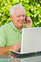 Smiling mature man talking on a cell phone and working with a laptop computer on outdoor patio table.