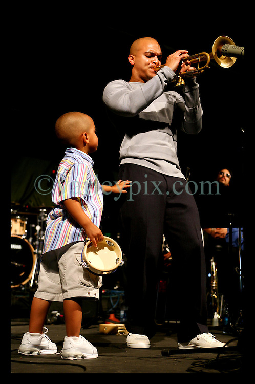 April 28nd, 2006. New Orleans, Louisiana. Jazzfest . The New Orleans Jazz and Heritage festival. Local jazz legend Irvin Mayfield with Irvin's young son Irvin Mayfield III  on stage at the Bellsouth WWOZ Jazz tent with the New Orleans Jazz orchestra.