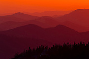 Numerous Sierra Nevada mountains and ridges are visible through a hazy, golden sunset above Kings Canyon in California. Among the peaks are Converse Mountain (foreground), Rogers Ridge (foreground center), 8167-foot (2489-meter) Patterson Mountain (background right), and 6697-foot (2041-meter) Dinkey Mountain (background left).