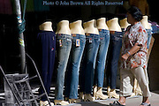A woman is walking past a store with a display of mannequins wearing denim blue jeans on a city street in Chiang Rai, Thailand.