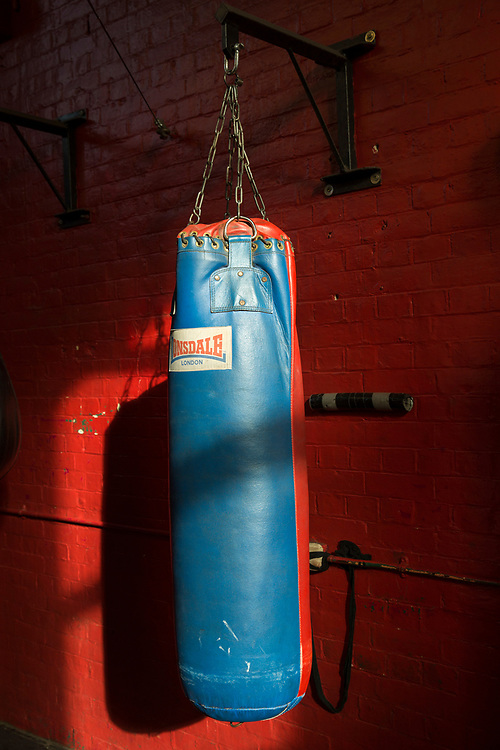 A single Lonsdale boxing punch bag hangs inside a boxing gym with red painted walls. Folkestone, Kent. (photo by Andrew Aitchison / In pictures via Getty Images)