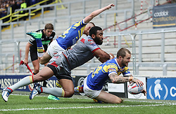 Leeds Rhinos Luke Briscoe goes over for a try past Catalans Dragons' Samisoni Langi, during the Betfred Super League match at Emerald Headingley Stadium, Leeds.