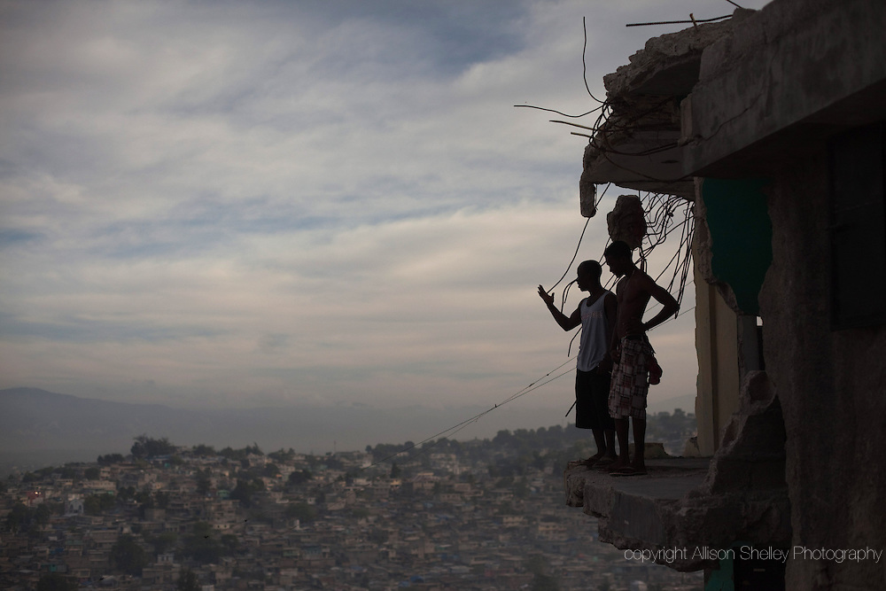 Horlich Florestal, 24, L, and Rosemond Altidon, 22, R, stand on the edge of their apartment building, half of which was destroyed in the earthquake of January 12, 2010, in the Fort National neighborhood of Port-au-Prince, January 9, 2011.