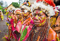 Woman from the Selehoto Alunumuno tribe standing in a group. Her face is painted and she is wearing traditional dress made from animal fur, flowers, feathers, beads and leaves. Photo taken by a small village in the Papua New Guinea highlands.