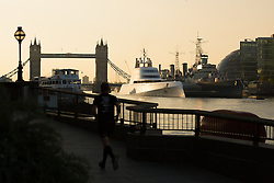 © Licensed to London News Pictures. 08/09/2016. LONDON, UK. A man jogs past a superyacht, known as 'Motor Yacht A' is seen moored next to HMS Belfast on the River Thames during the morning light. Motor Yacht A is owned by Russian billionaire, Andrey Melnichenko (known as the King of Bling). The stunning 390ft super yacht design is inspired by a submarine and was designed by Philippe Starck. It has been reported that Melnichenko is currently building a new super yacht and Motor Yacht A will be put up for sale.<br /> Photo credit: Vickie Flores/LNP