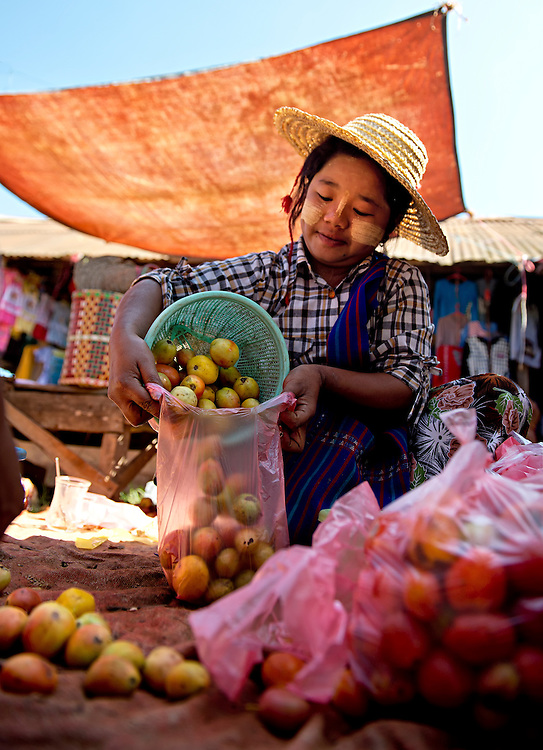 A girl packing fruit in a market, Myanmar.
