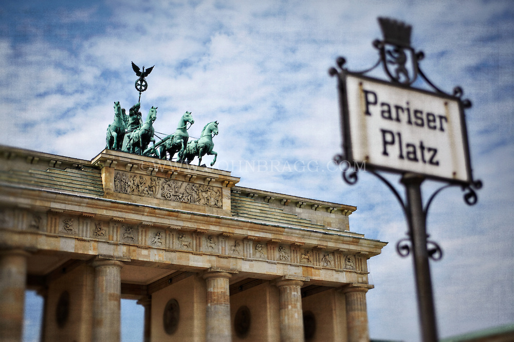 The Brandenburg Gate and decorative Pariser Platz sign with a cloudy sky in Berlin, Germany.