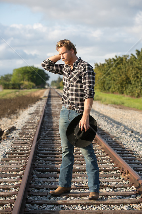 moody cowboy standing on railroad tracks