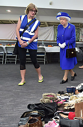 Queen Elizabeth II looks at donations to members of the community affected by the fire at Grenfell Tower in west London during a visit to the Westway Sports Centre which is providing temporary shelter for those who have been made homeless in the disaster.