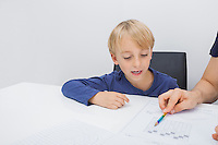 Cropped image of father assisting boy in studies