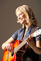 Woman Playing Guitar smiling low angle view