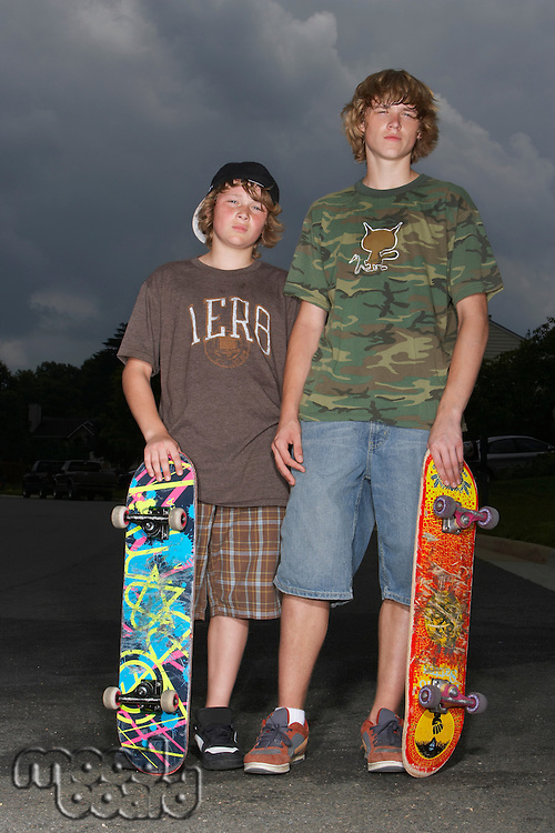 Two adolescent boys (13-17) with skateboards standing outdoors portrait