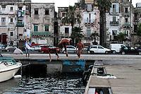 Bambini si divertono a tuffarsi dal pontile sul lungomare della città vecchia.