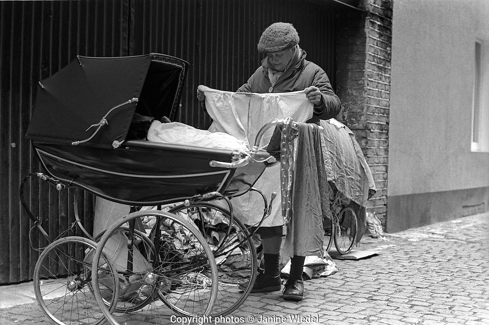 Homeless woman who sleeps under her two prams sorting out and airing her belongings in Knightsbridge London 1970s
