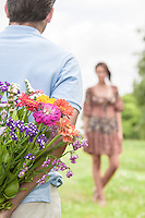 Cropped image of man surprising woman with bouquet in park