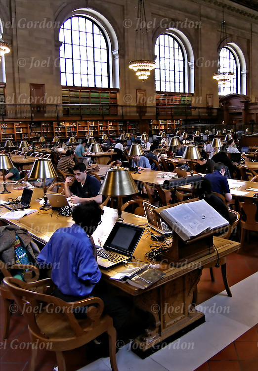 Reference Room in the Fifth Avenue branch of the New York Public Library. College students researching in library,using personal computer and library computer to researching on the internet.