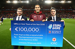 LIVERPOOL, ENGLAND - Tuesday, February 19, 2019: Liverpool defender Virgil van Dijk with a cheque of €100,000 for the International Committee of the Red Cross, pictured with UEFA vice-president Michele Uva and ICRC's Martin Schüepp during the UEFA Champions League Round of 16 1st Leg match between Liverpool FC and FC Bayern München at Anfield. (Pic by Jan Kruger - UEFA)