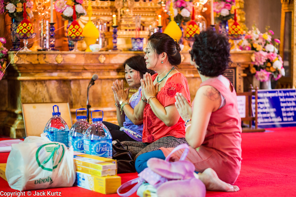 15 JULY 2014 - BANGKOK, THAILAND:  Women pray in the ubosot (ordination hall) at Wat Rachathiwat Ratchaworawihan on Samsen Soi 9. The temple has a large teak instruction hall, considered one of the finest teak buildings in Asia.   PHOTO BY JACK KURTZ