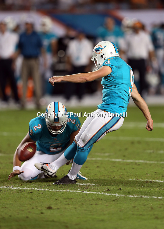 Miami Dolphins punter Brandon Fields (2) holds as Miami Dolphins kicker Caleb Sturgis (9) kicks a second quarter field goal good for a 10-3 lead during the NFL week 9 football game against the Cincinnati Bengals on Thursday, Oct. 31, 2013 in Miami Gardens, Fla.. The Dolphins won the game 22-20 in overtime. ©Paul Anthony Spinelli