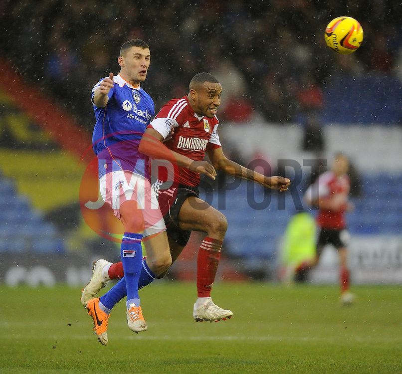 Oldham Athletic's James Wilson heads home under pressure from Bristol City's Tyrone Barnett - Photo mandatory by-line: Joe Meredith/JMP - Tel: Mobile: 07966 386802 08/02/2014 - SPORT - FOOTBALL - Oldham - Boundary Park - Oldham Athletic v Bristol City - Sky Bet League One