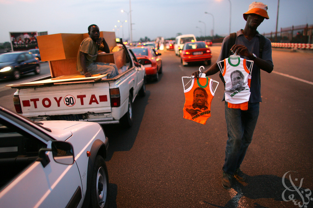 A street vendor sells shirts adorned with the image of Ivorian national/Chelsea footballer Didier Drogba during rush hour in the Plateau district of Abidjan, Côte d'Ivoire February 17,2006. Football is an integral part of the social fabric that makes up Ivorian society.