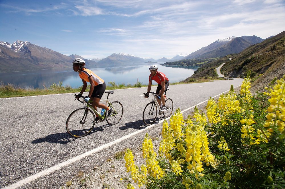 Two road bike riders with lake and majestic mountains in the background.