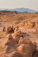 Odd shaped hoodoos of Entrada Sandstone illuminated in eveing afterglow, Goblin Valley State Park Utah USA
