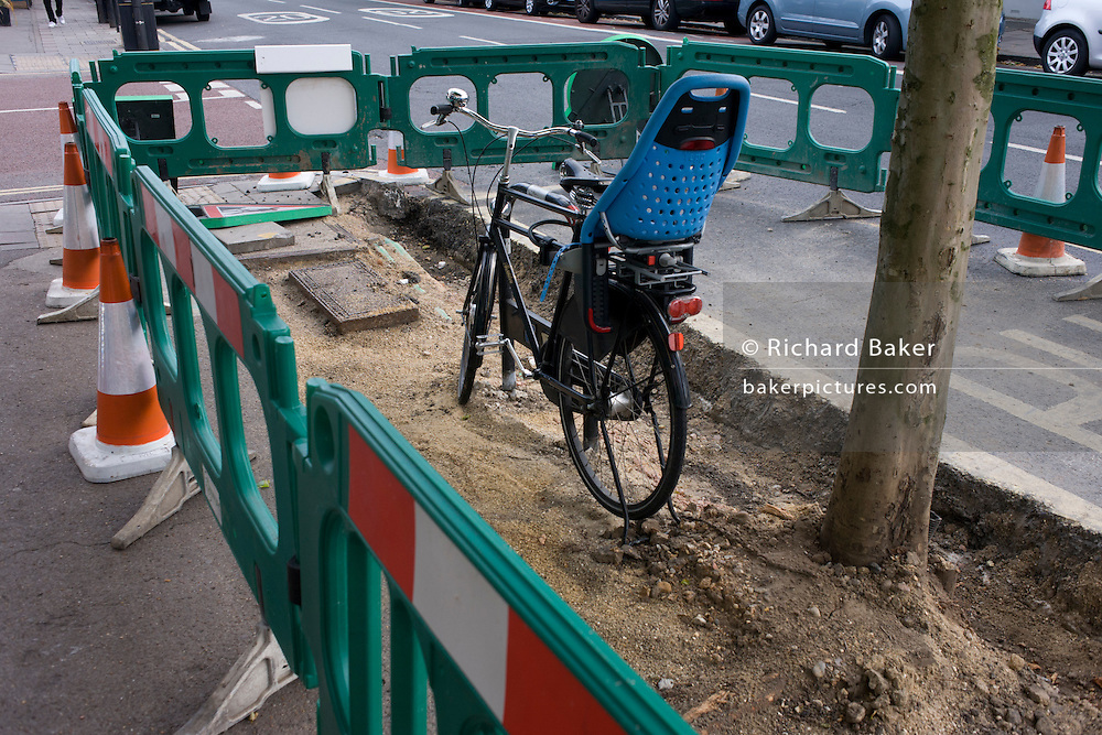 A ladies' bicycle locked to a post, enclosed and blocked in during pavement replacement works in south London.