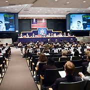 "Commission staffers present Staff Statement No. 16, ""Outline of the 9/11 Plot."" On the screen is security camera footage of Mohamed Atta. The 9/11 Commission's 12th public hearing on ""The 9/11 Plot"" and ""National Crisis Management"" was held June 16-17, 2004, in Washington, DC."