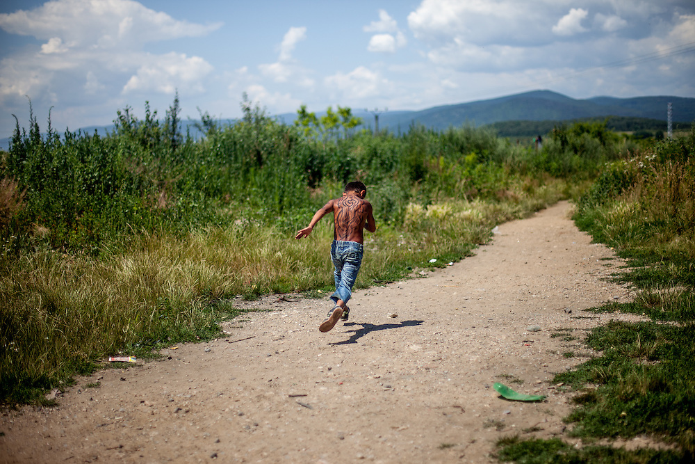 "A young boy with painted back of his body is running on a path towards river ""Bodva"" to cool down on a tropical day. The Roma settlement ""Budulovska"" is segregated from the city Moldava nad Bodvou and is located in the fields behind."