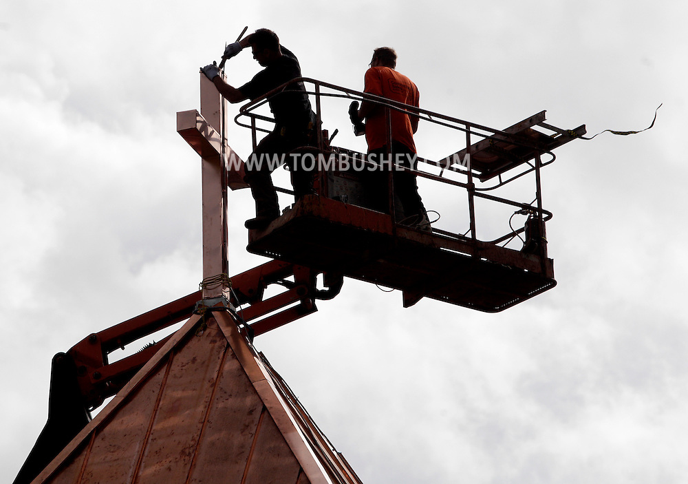 orkers from Eden Restoration install copper on the cross on top of St. Stanislaus Church in Pine Island on Wednesday, April 27, 2011. The cross on top of the bell tower is about 75 feet high. The entire roof will be covered in copper in the project at the church, which will be celebrating its 100th anniversary in June 2012.