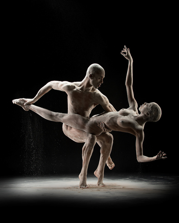 Pax de duex of two contemporary ballet dancers in the nude with flour. Shot in the studio against a dark background. Photographed by dance photographer, Rachel Neville.