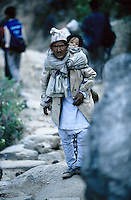 Somewhere in Kalikot, 05 March 2005...A father carring his daughter. In most of the Kalikot area, walking is the only method of transport. Donkeys are also used for moving cargo.