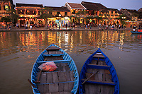 Wooden boats moored on the Thu Bon river opposite Bach Dang Street in the old town of Hoi An, Vietnam