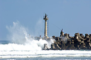 Men fish from a jetty as big waves crash in Fulong, Taiwan.
