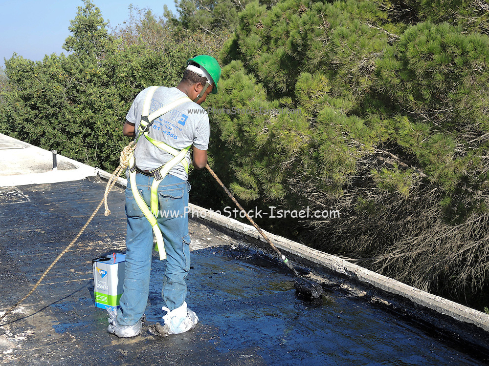 Roofer water seals a roof with tar