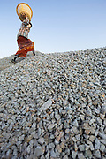 Woman carries heavy basket of rocks to top of pile, Myiek