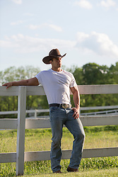 rugged cowboy leaning against a fence on a ranch at sunset