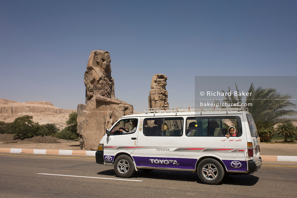 Egyptians in a minibus drive past the ancient Egyptian Colossi of Memnon site, Luxor, Nile Valley, Egypt. The Colossi of Memnon (memorial temple of Amenophis III) are two massive stone statues of Pharaoh Amenhotep III, who reigned during Dynasty XVIII. For the past 3,400 years (since 1350 BC) they have stood in the Theban necropolis, west of the River Nile from the modern city of Luxor.