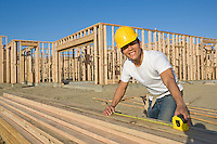 Construction worker measuring wooden planks